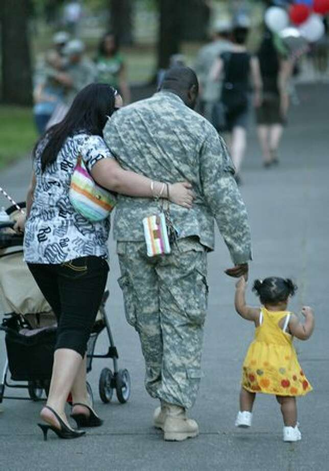 Damon Pickens walks with wife Siabhon Pickens and daughter Mariah, 1, after he and other members of the Stryker Brigade returned to Fort Lewis, Sept. 10, 2007. Photo: P-I File