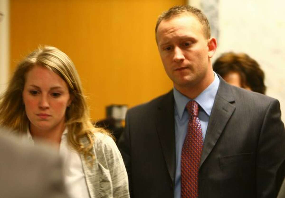 Seattle Police officer Ian Birk, center, walks into the courtroom with his wife Camielle on Thursday at the King County Courthouse in Seattle. Seattle Police Officer Ian Birk sat before an inquest jury after shooting and killing Native American woodcarver John T. Williams last August.