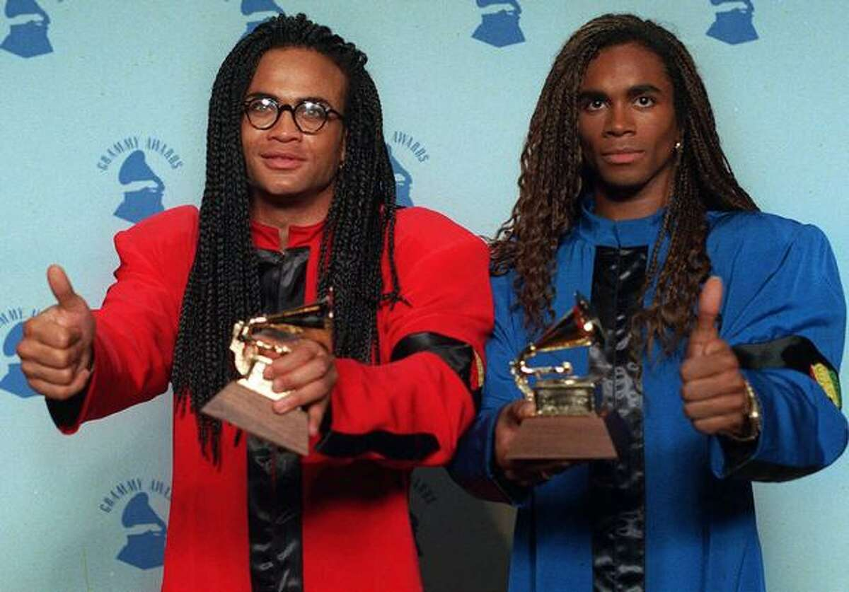 Rob Pilatus (1965-1998), left, and Fabrice Morvan of Milli Vanilli give the thumbs-up as they display their Grammys for Best New Artist in Los Angeles in this Feb. 21, 1990 file photo. (AP Photo/Douglas C. Pizac, File)