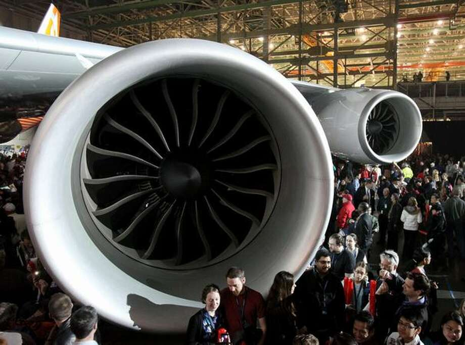 People gather around a General Electric GEnx engine on Boeing's new 747-8 Intercontinental during the unveiling ceremony for the new airplane at the Boeing plant in Everett. Photo: Joshua Trujillo, Seattlepi.com