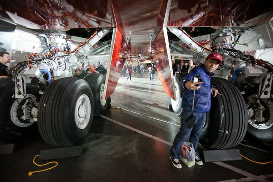 People gather under the belly of Boeing's new 747-8 Intercontinental during the unveiling ceremony for the new airplane at the Boeing plant in Everett. Photo: Joshua Trujillo, Seattlepi.com