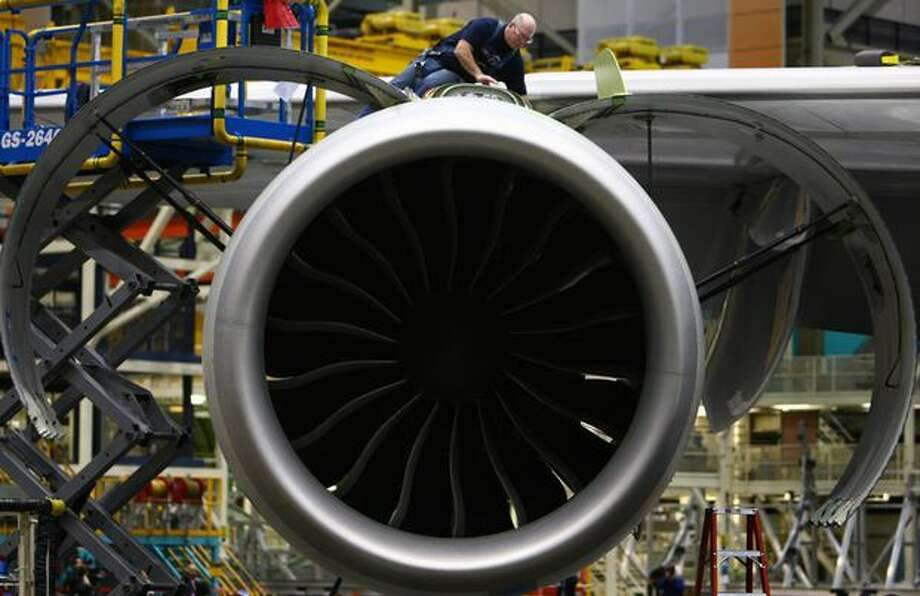 Boeing employee Mike Millenaar works atop a GEnx engine on a Boeing 747-8 Intercontinental, seen during a tour of the Boeing 747-8 Intercontinental and Freighter assembly line on Saturday, February 12, 2011 at the Boeing plant in Everett. Photo: Joshua Trujillo, Seattlepi.com