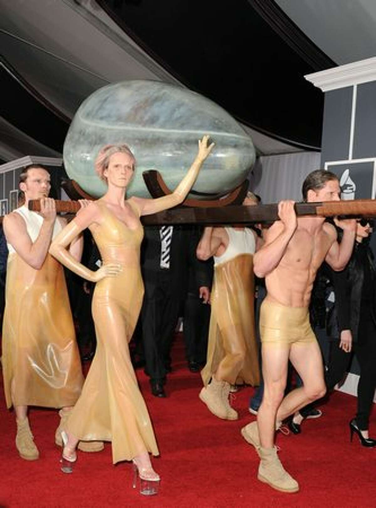 We included Lady Gaga (inside her egg) in this compilation because, even though you can't see her, she's redefining what it means to make a red-carpet entrance. Besides, we think the egg is attractive, and the egg bearers -- and the willowy caretaker at center -- enhance the overall effect. Well played, Gaga.