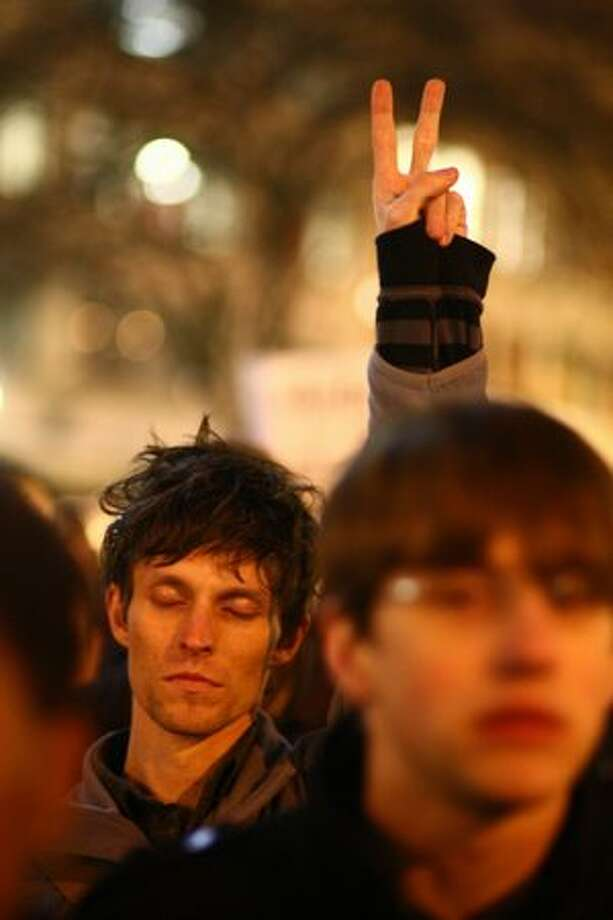 Adam Prometheus shows a peace sign as protesters gather at Westlake Park. Photo: Joshua Trujillo, Seattlepi.com