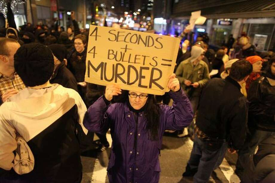 Karla Manus holds a sign as protesters march in downtown Seattle. Photo: Joshua Trujillo, Seattlepi.com