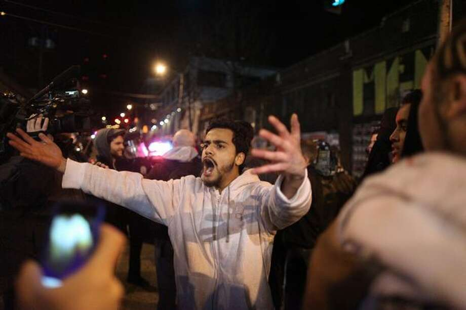 A protester taunts Seattle Police officers in the Capitol Hill neighborhood. The man yelled for violence against the police but was shouted down by others in the crowd. Photo: Joshua Trujillo, Seattlepi.com