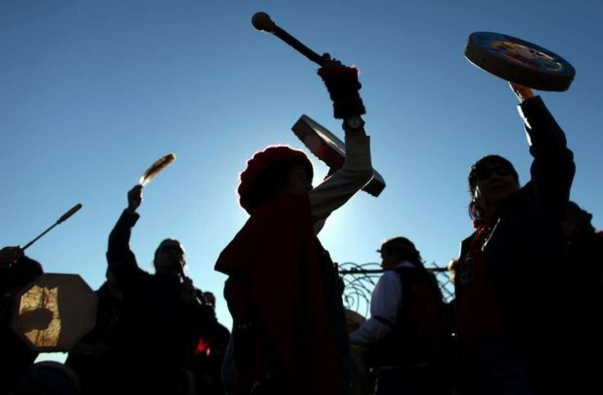Teri Hanlon, center, raises her drum with others during a rally and