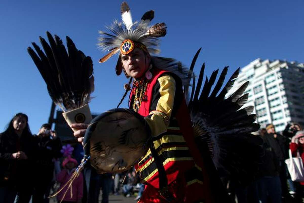 Traditional pow-wow dancer Mark Sison performs a crow hop dance during the rally.