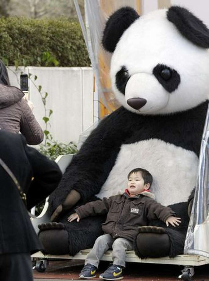 A mother takes a photo of a her son posing with a stuffed giant panda at Tokyo's Ueno Zoo Friday, Feb. 18, 2011. People are getting ready to welcome two giant pandas arriving Monday, Feb. 21 to the zoo from China on a 10-year loan, the latest installment of panda diplomacy aimed at warming the two countries' often-strained relations. (AP Photo/Koji Sasahara) Photo: Associated Press