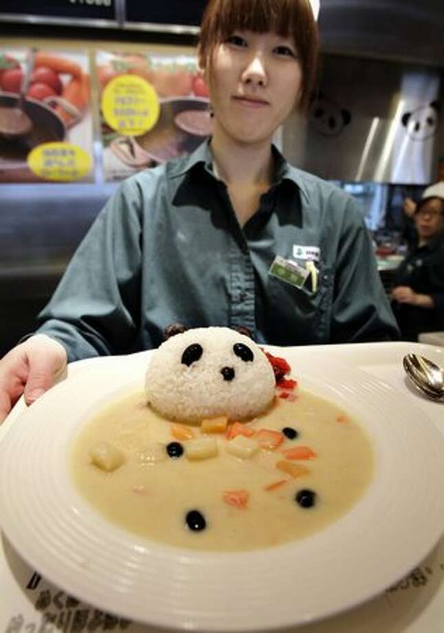 Ueno Green Saloon restaurant staff Eri Nakawake shows its new menu Panda Curry in Tokyo's Ueno district Friday, Feb. 18, 2011. People in the area are getting ready to welcome two giant pandas arriving Monday, Feb. 21 to Tokyo's Ueno Zoo from China on a 10-year loan, the latest installment of panda diplomacy aimed at warming the two countries' often-strained relations. (AP Photo/Koji Sasahara) Photo: Associated Press