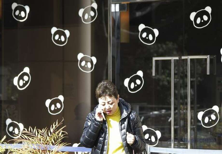 A woman comes out from a restaurant decorated its windows with panda characters in Tokyo's Ueno district Friday, Feb. 18, 2011. Shops, restaurants and people near Tokyo's Ueno Zoo are getting ready to welcome two giant pandas arriving Monday, Feb. 21 to the zoo from China on a 10-year loan, the latest installment of panda diplomacy aimed at warming the two countries' often-strained relations. (AP Photo/Koji Sasahara) Photo: Associated Press
