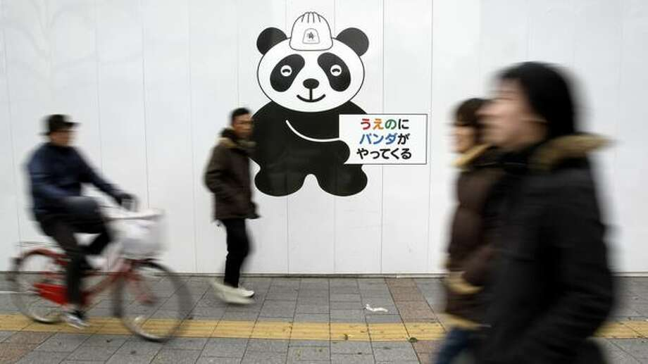 "People pass by a construction site wall painted with a panda character holding a sign reading: ""Pandas are coming to Ueno"" in Tokyo Friday, Feb. 18, 2011. Shops, restaurants and people in the area near Tokyo's Ueno Zoo are getting ready to welcome two giant pandas arriving Monday, Feb. 21 from China on a 10-year loan, the latest installment of panda diplomacy aimed at warming the two countries' often-strained relations. (AP Photo/Koji Sasahara) Photo: Associated Press"