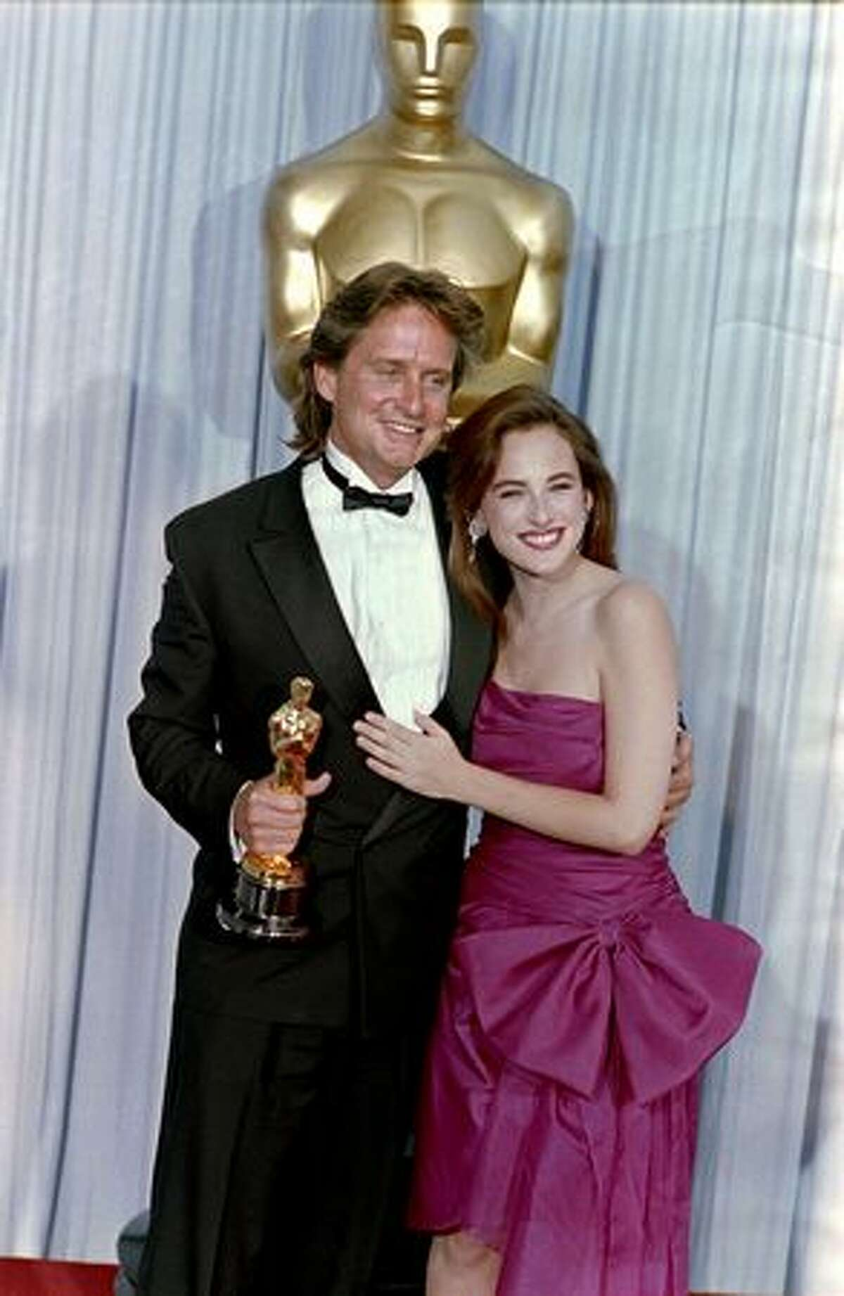 1988: Actor Michael Douglas, accompanied by actress Marlee Matlin, poses with his Best Actor Oscar for the film