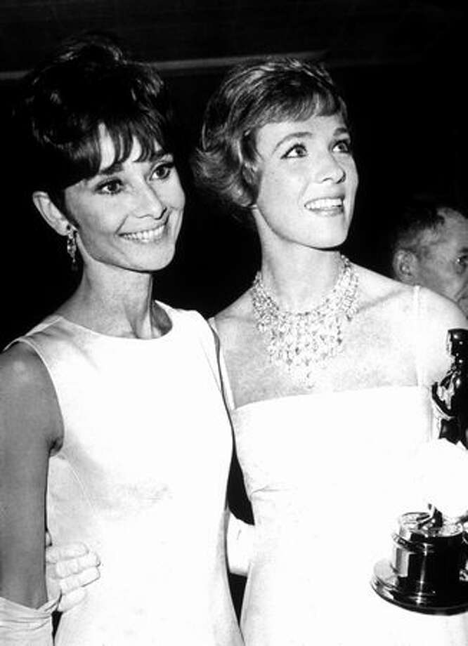 "1965: Actress Julie Andrews (right) holds her Oscar while standing with actress Audrey Hepburn (1929 - 1983) at the Academy Awards ceremonies in Santa Monica, Calif. Andrews won Best Actress for her performance in the film ""Mary Poppins,"" directed by Robert Stephenson. Photo: Getty Images"