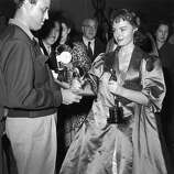 "1954: Actress Donna Reed (1921 - 1986) signs an autograph while holding her Oscar at the Academy Awards, Los Angeles. Reed won Best Supporting Actress for her role in ""From Here to Eternity."""
