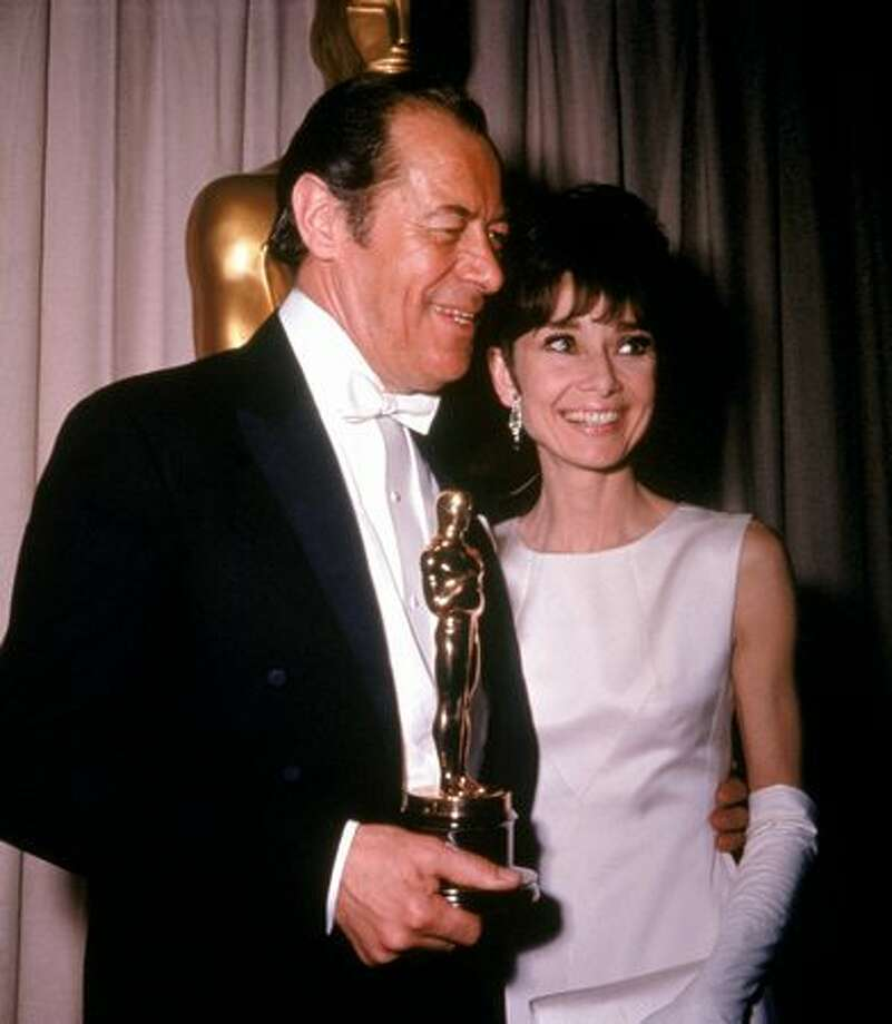 "1965: Actor Rex Harrison (1908 - 1990) holds his Best Actor Oscar for the film, ""My Fair Lady,"" while standing with his co-star, actress Audrey Hepburn (1929 - 1993), during the Academy Award ceremonies, Santa Monica, Calif. The film was directed by George Cukor. Photo: Getty Images"