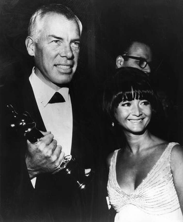 "1966: Actor Lee Marvin (1924 - 1987) with Michelle Triola (1932 - 2009), holding the Academy Award Oscar for best actor which he won for the film ""Cat Ballou."" Triola later unsuccessfully sued Marvin for support payments even though they had never been married, introducing the word ""palimony"" into common dialogue. Photo: Getty Images"