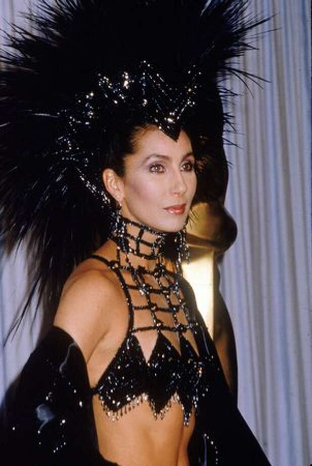 1986: Actress/singer Cher attends the Academy Awards ceremony, wearing a black headdress, at the Dorothy Chandler Pavilion, Los Angeles. Photo: Getty Images