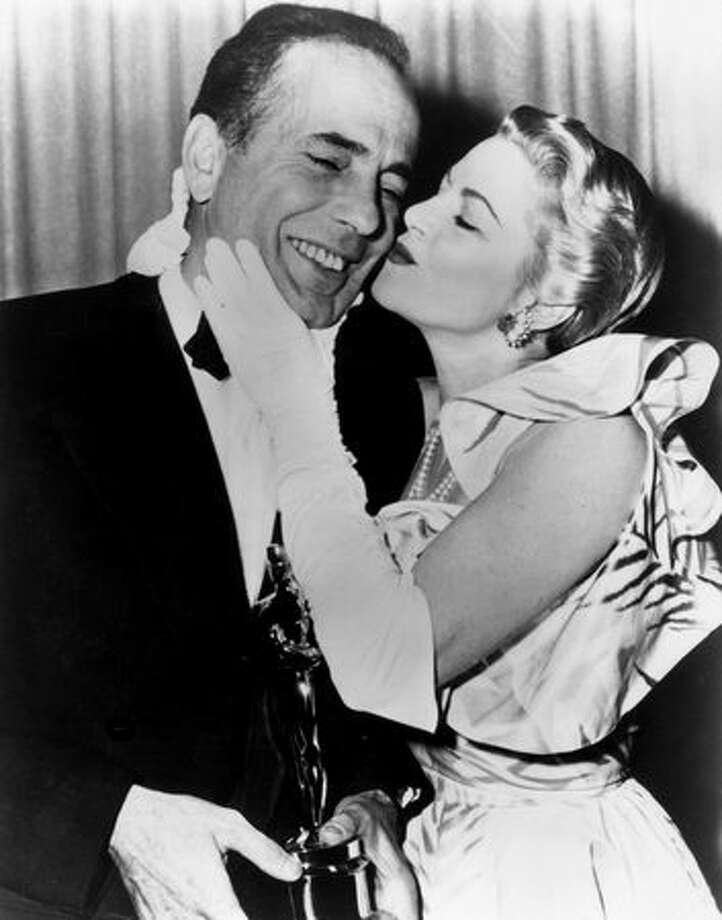 "1952: Actor Humphrey Bogart (1899-1957) receives a kiss from actress Claire Trevor (1909 - 2000) while standing backstage with the Best Actor Oscar he won for his role in director John Huston's film, ""The African Queen,"" at the RKO Pantages Theatre in Los Angeles. Photo: Getty Images"