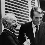 1970: Celebrated pianist Arthur Rubinstein (1887 - 1982) receiving the Documentary Feature Oscar from Gregory Peck (1916 - 2003) in the Parisian residence of the great musician.