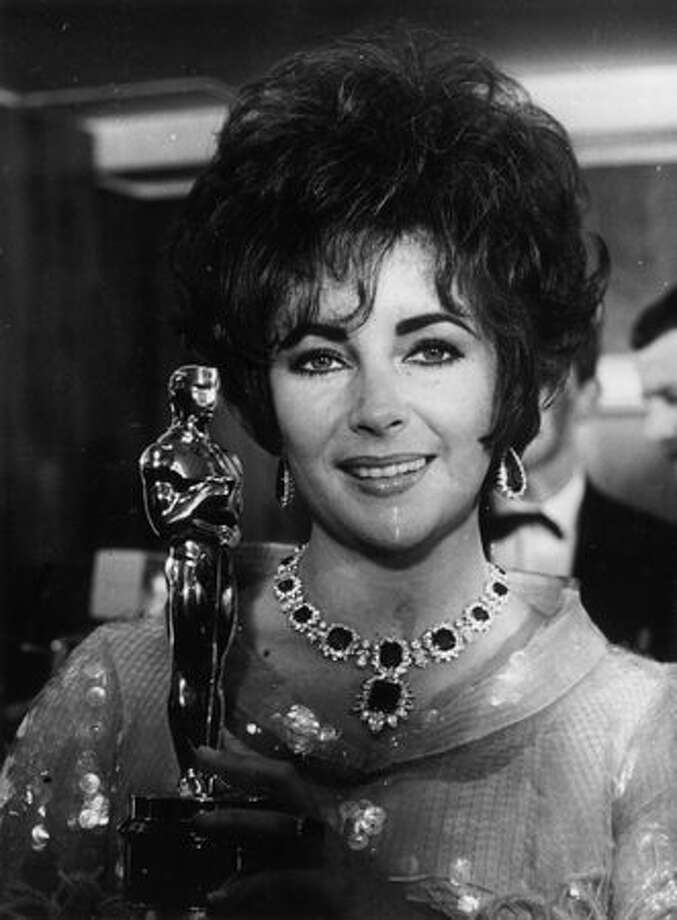 "1967: Elizabeth Taylor holding an Oscar she won for the film ""Who's afraid of Virginia Woolf"" at the Grosvenor Hotel, London. Photo: Getty Images"