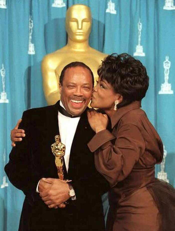 1995: TV talk show host Oprah Winfrey kisses musician Quincy Jones after he received the Jean Hersholt Award at the 67th Academy Awards in Los Angeles. The Hersholt Award is given for humanitarian work done by a member of the entertainment industry. Photo: Getty Images