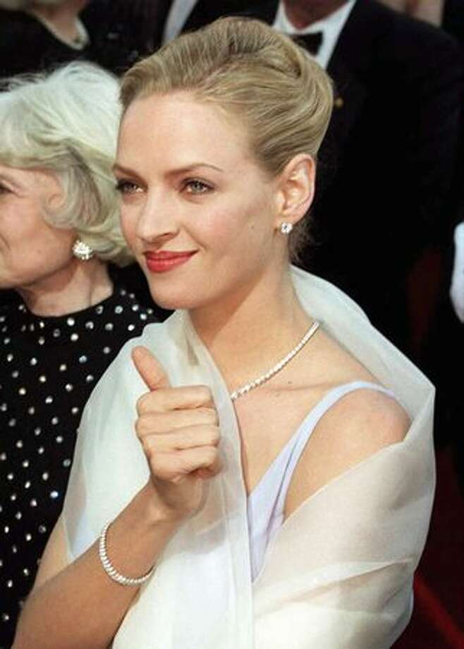 "1995: Actress Uma Thurman gives a thumb's up as she is greeted by fans as she arrives for the 67th annual Academy Awards in Los Angeles. Thurman was nominated for best supporting actress for her role in ""Pulp Fiction."" Photo: Getty Images"