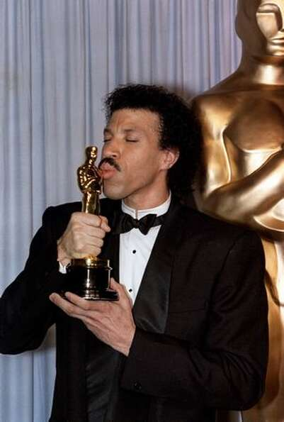 1986: Singer Lionel Richie kisses his Oscar after he was awarded he golden statue at the 58th annual