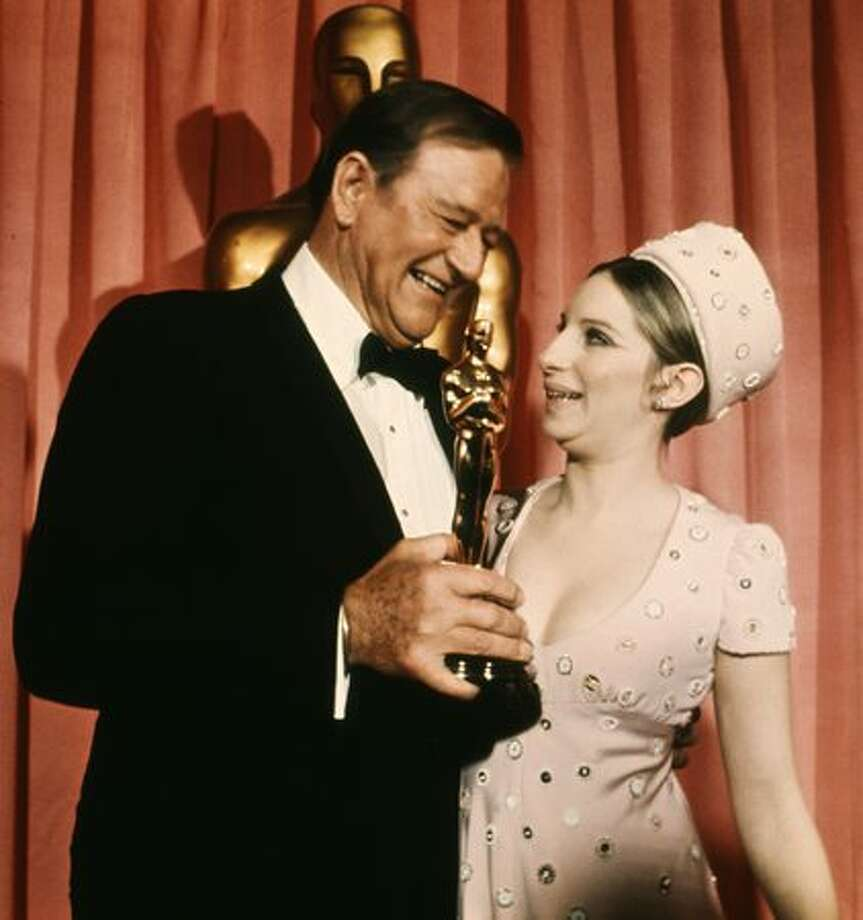 "1969: Actor John Wayne (1907 - 1979) holds an Oscar that he was awarded for his role in ""True Grit."" On right, actress/singer Barbra Streisand. Photo: Getty Images"