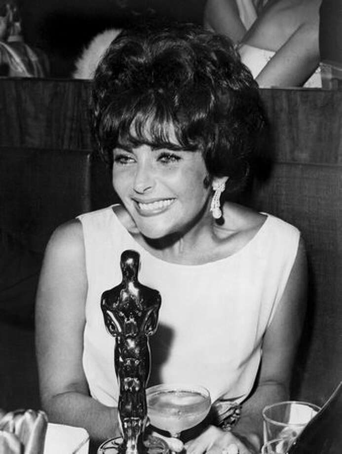 "1961: Elizabeth Taylor with her Oscar at a presentation party after being named Best Actress for her part in ""Butterfield 8."" Photo: Getty Images"