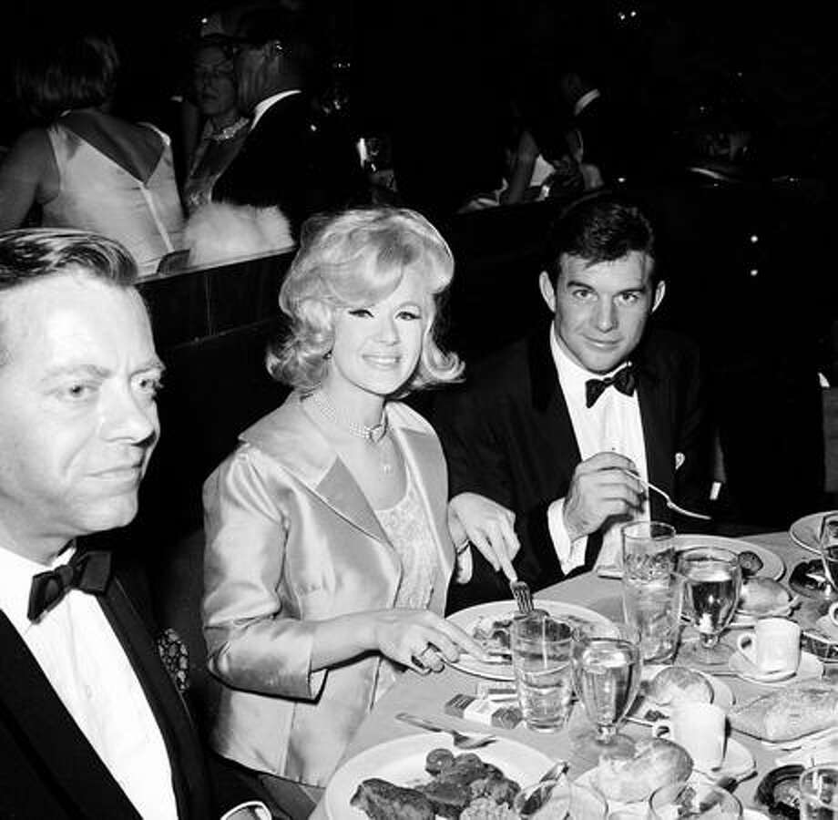 1964: Actress Connie Stevens, her husband James Stacy (right) and actor Max Showalter (1917 - 2000) eat during the Academy Awards ceremonies, Santa Monica, Calif. Photo: Getty Images
