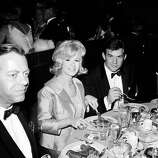 1964: Actress Connie Stevens, her husband James Stacy (right) and actor Max Showalter (1917 - 2000) eat during the Academy Awards ceremonies, Santa Monica, Calif.