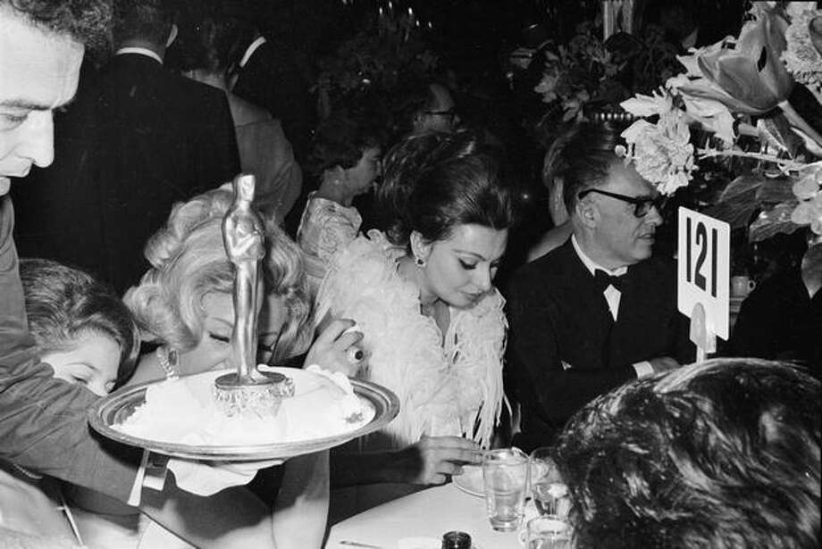 1963: Actress Sophia Loren eats at the Academy Awards ceremony in Santa Monica, Calif., as a waiter walks by with an Oscar. Photo: Getty Images