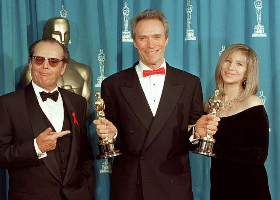 "1993: Clint Eastwood holds up his two Oscars at the 65th annual Academy Awards. He won for Best Director and Best Picture for ""Unforgiven,"" Eastwood poses with presenters, actor Jack Nicholson and entertainer Barbra Streisand. Photo: Getty Images"
