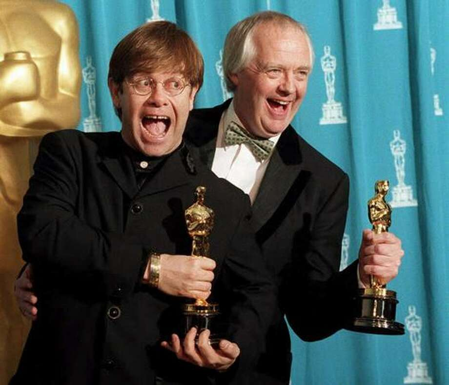"1995: Singer and songwriter Elton John (left) poses with partner Tim Rice at the 67th annual Academy Awards in Los Angeles. John and Rice won Oscars for their original song ""Can You Feel the Love Tonight?"" from the film ""The Lion King."" Photo: Getty Images"