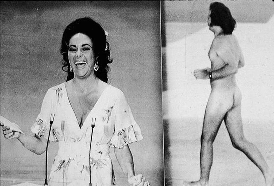1974: Actress Elizabeth Taylor laughs as she remarks that she was upstaged by streaker Robert Opal before presenting the Oscar for Best Picture at the 46th annual Academy Awards ceremony, Los Angeles. At right, Opal darts across the stage naked just as David Niven was introducing Taylor. Photo: Getty Images