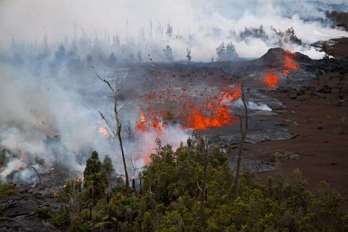In this photo taken Sunday and provided by the U.S. Geological Survey, Lava spatters above the fissure just west of the base of Pu'u O'o crater. Scientists are monitoring a new vent that has opened at the Kilauea volcano, sending lava shooting up to 65 feet high. (AP Photo/US Geological Survey)