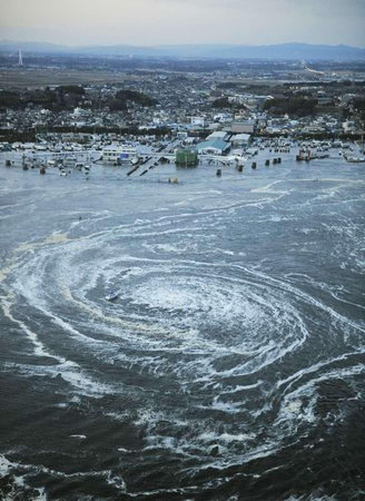 Tsunami swirls near a port in Oarai, Ibaraki Prefecture. (AP Photo/Kyodo News)