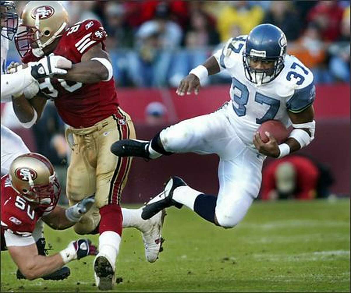 Seattle running back Shawn Alexander gets tripped up by 49ers linebacker Derek Smith after a short gain in the second quarter. Aleander scored the game-tying touchdown a few plays later in the Seahawks' 24-17 win.