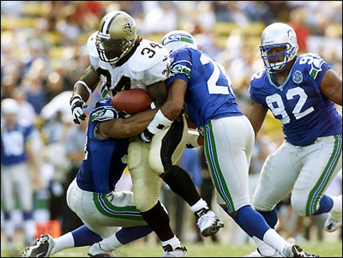 Saints' Ricky Williams is brought down by Seahawks safety Kerry Joseph and an unidentified player in the fourth quarter.