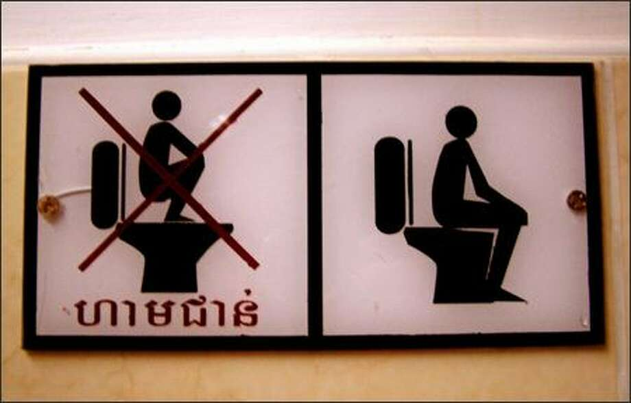 "At the ancient ruins of Angkor Wat in Cambodia a sign helps clarify for visitors the proper way to use ""western-style"" toilets. Photo: Winda Benedetti, Special To Seattle Post-Intelligencer"
