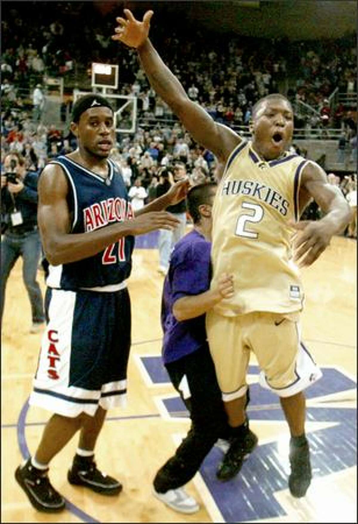 Nate Robinson celebrates the Huskies' win over Arizona as the Wildcats' Hassan Adams finds his way off the floor.