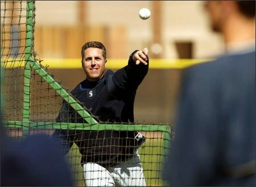 Mariners pitching coach Bryan Price tosses a ball in Peoria, Ariz.