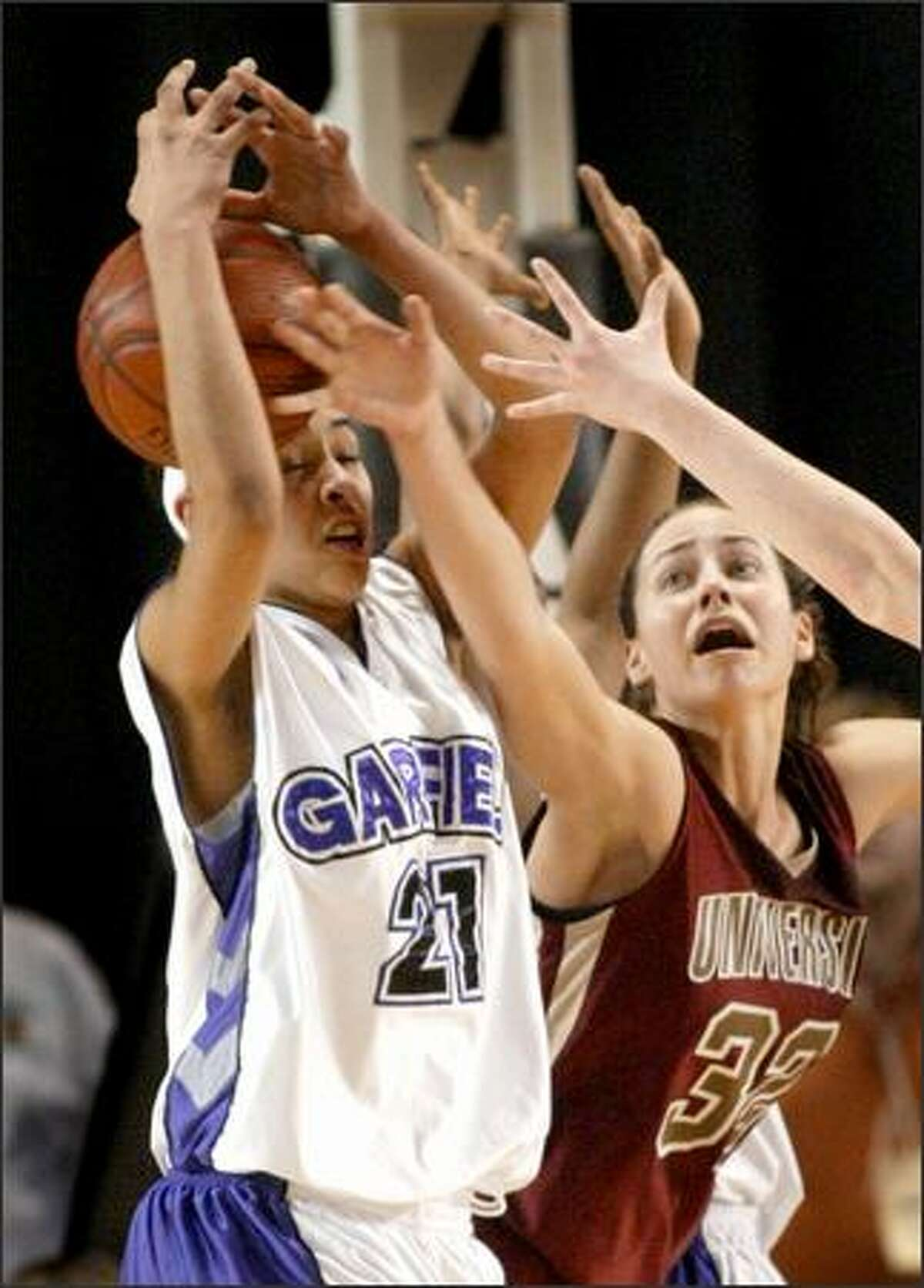 While Garfield's Samantha Tinned tries to find the handle on a rebound late in the fourth quarter, University's Jami Bjorklund tries in vain to pry the ball loose.