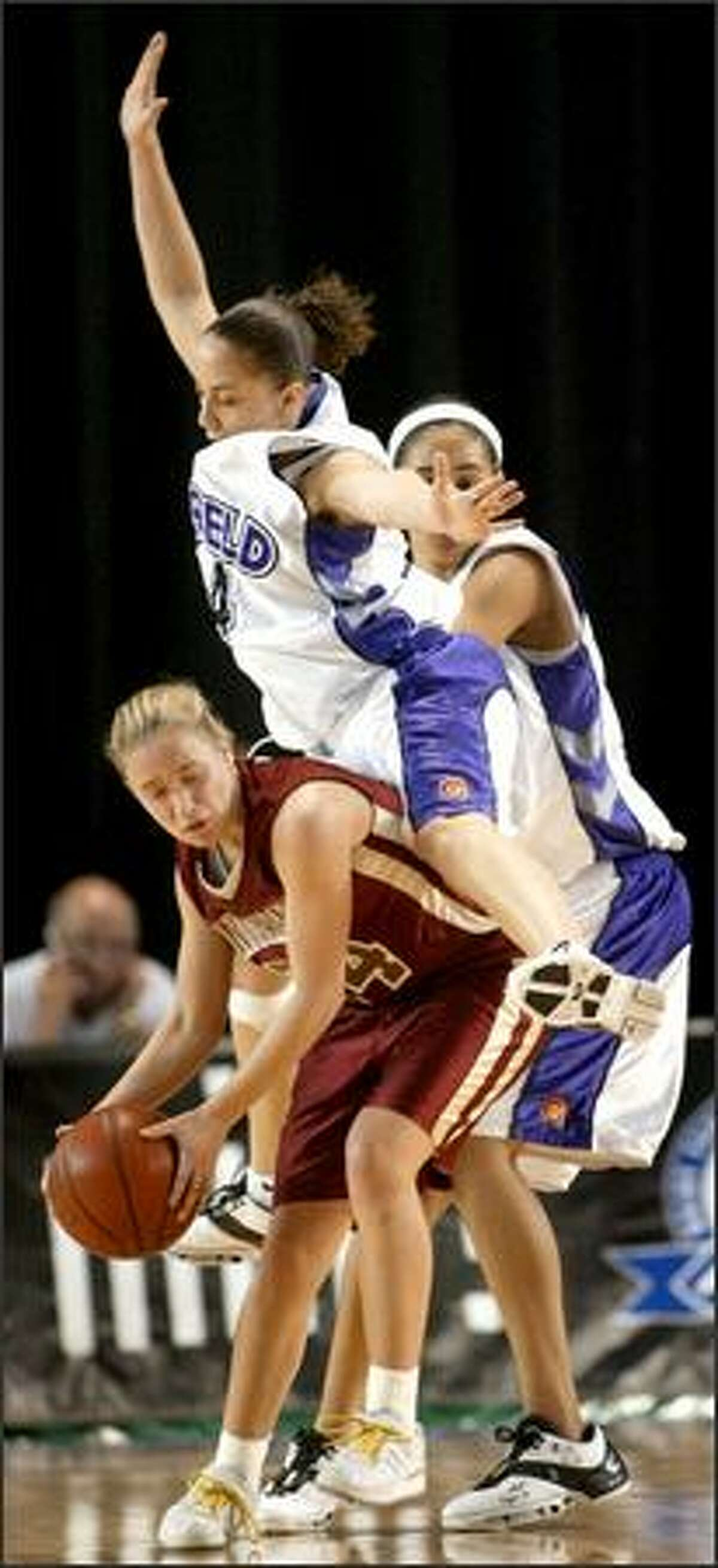 Garfield's Malia O'Neal fouls University counterpart Tonya Schnibble during the Bulldogs' victory.
