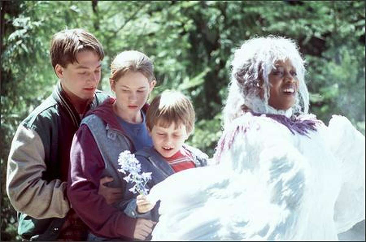 A transformed Mrs. Whatsit (Alfre Woodard, right) carries Calvin (Gregory Smith), Meg (Katie Stuart) and Charles Wallace (David Dorfman) off on their adventures across space and time.