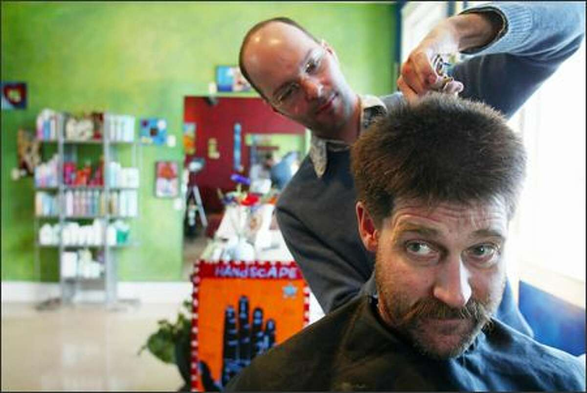 Stylist Patrick Bertels at work on the very thick hair of Bellingham contractor John Harris. Harris was chosen to be the makover subject of five Bellingham area gay men in their