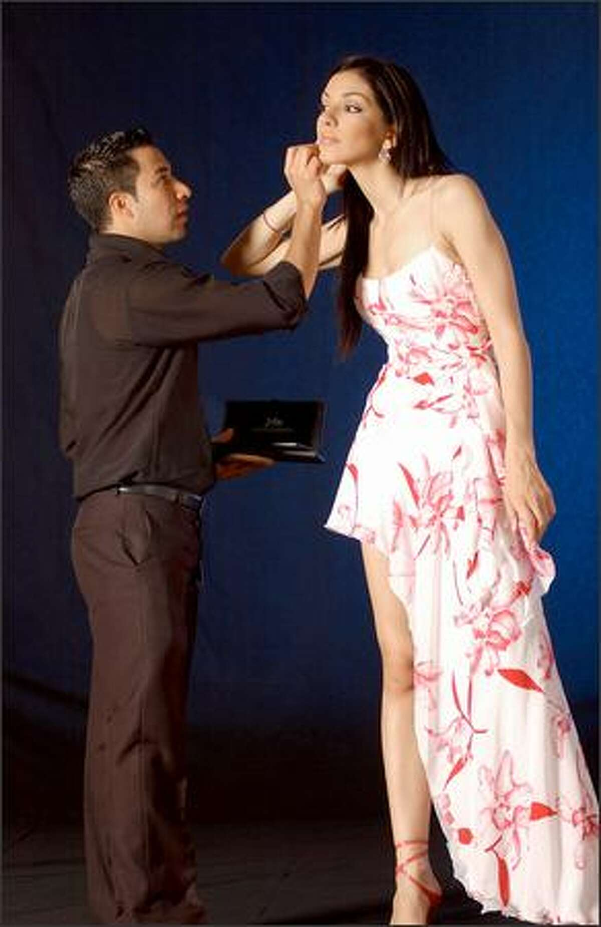 Jimmy Gomez applies finishing touches to Miss Greece, Valia Kakouti prior to official program book photo shoot at the JW Marriott Hotel in Quito, Ecuador.