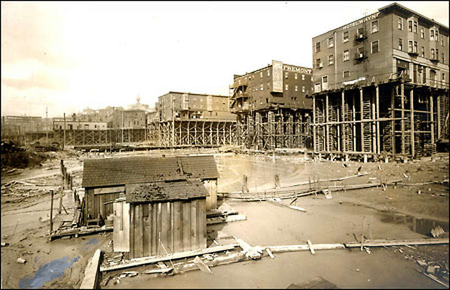 Seattle's backside, 1890s: A shack sits on the mudflats along Seattle's waterfront in the 1890s roughly in the area of Third and Fourth avenues south. The city's downtown area was a large land-reclamation project, with hills reduced and vast mudflats filled in. Buildings have been raised to their new level awaiting fill from the hills to the east. Photo: Seattle Post-Intelligencer
