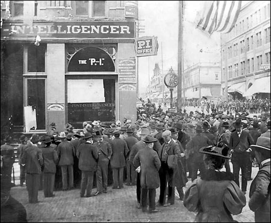 It was in the P-I: Crowds gather around the Post-Intelligencer building at Second Avenue and Cherry Street in 1898 to read news bulletins from the Spanish-American War. At the turn of the century, breaking news was often posted in the newspaper office's windows. Photo: Seattle Post-Intelligencer